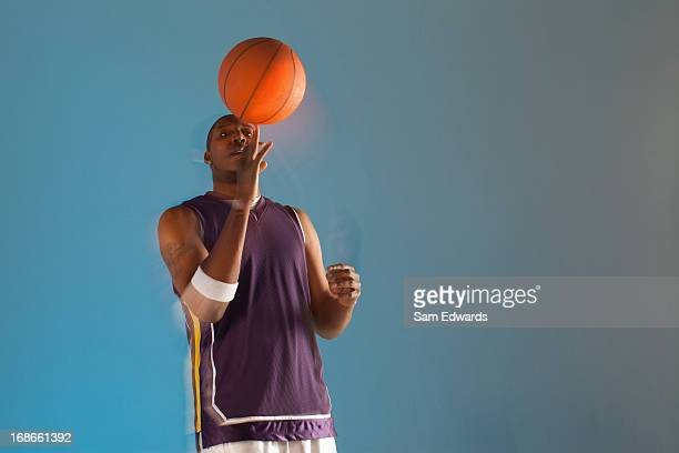 Basketball player balancing ball on one finger