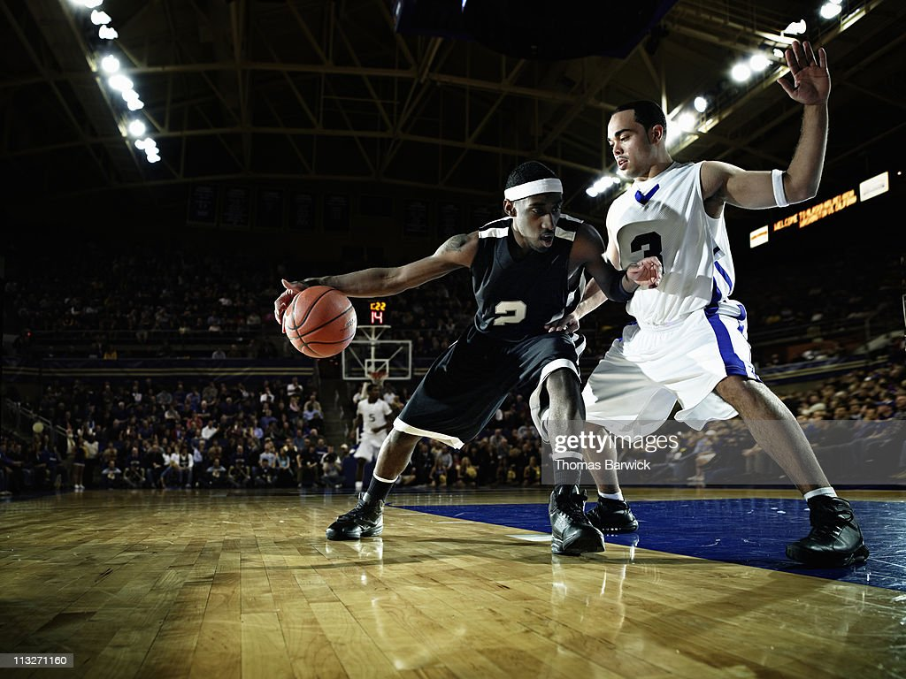 Basketball player being guarded by defender : Stock Photo