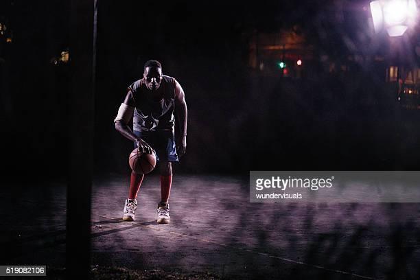 Driblar pelota de baloncesto en Corte en la noche