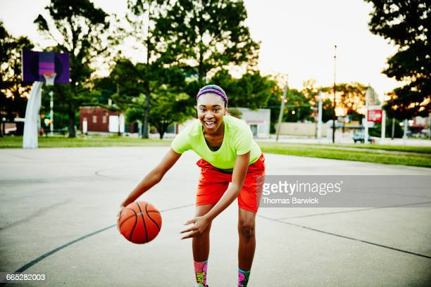 Basketball player dribbling ball on outdoor court