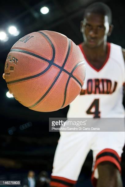 Basketball player dribbling basketball, low angle view