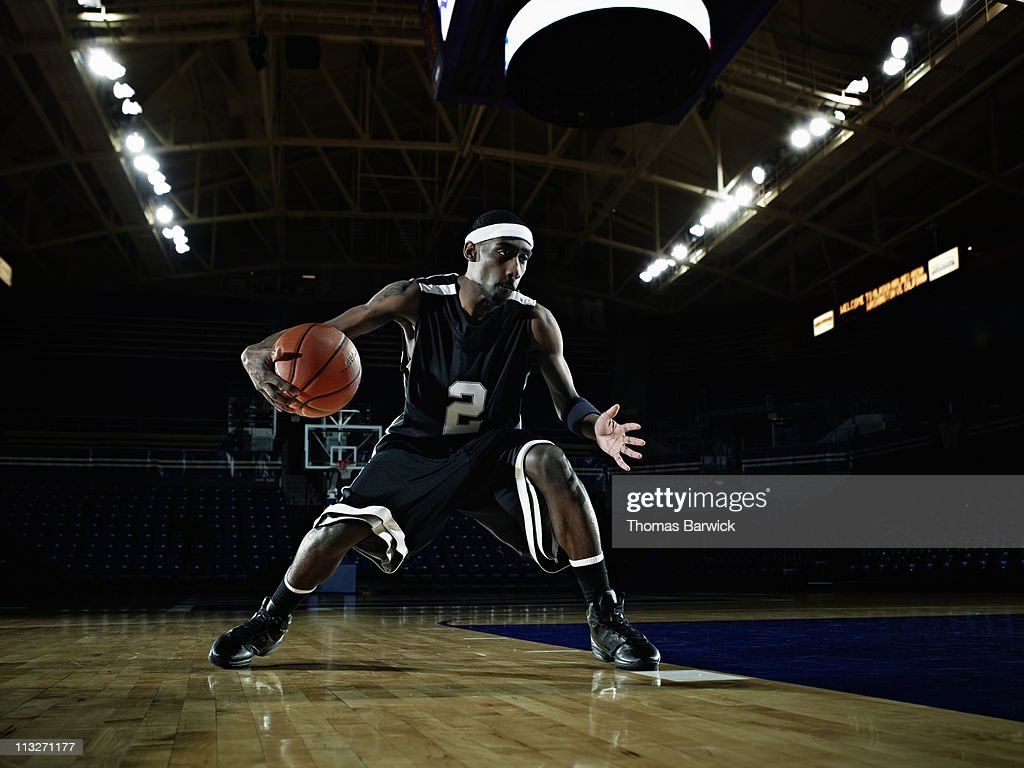 Basketball player dribbling basketball on court