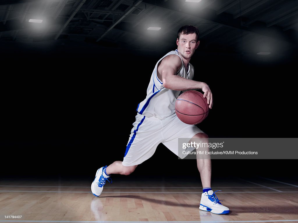 Basketball player dribbling on court : Stock Photo