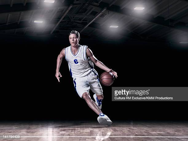 Basketball player dribbling on court