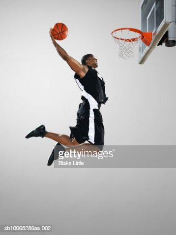 Basketball player dunking ball, low angle view