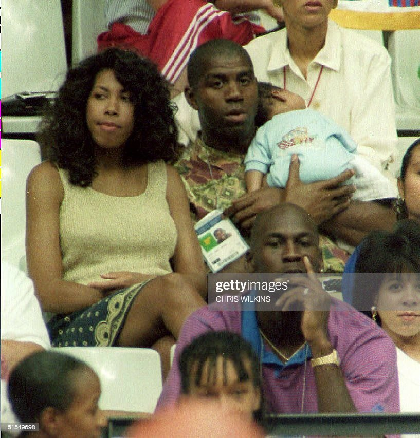 S basketball player Earvin 'Magic' Johnson holds his son Earvin Johnson III while watching the US women's basketball team play Spain 03 August 1992...