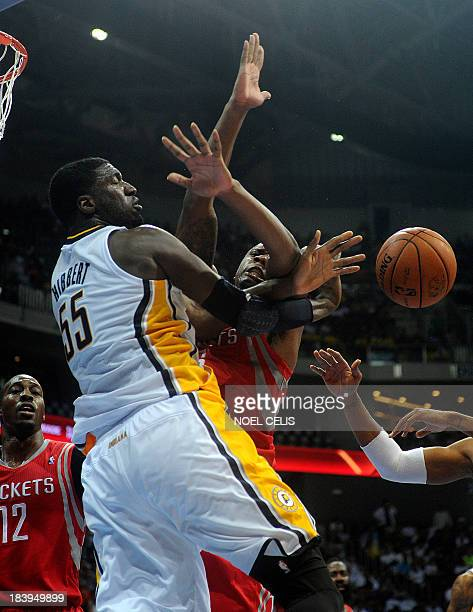 US basketball player for the Houston Rockets Terrence Jones drives the ball to the basket as Indiana Pacers Roy Hibbert attempts to block during the...