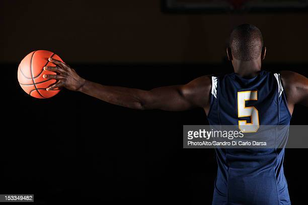 Basketball player holding basketball in hand, rear view