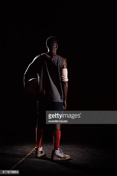 Basketball Player Holding Basketball on Hip in Night