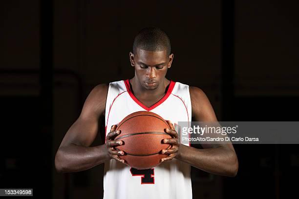 Basketball player holding basketball, portrait