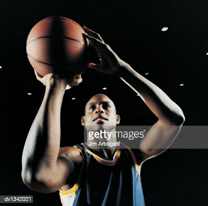 Basketball Player Holding the Ball and Looking Up to Aim : Stock Photo