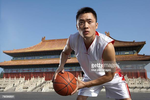 A basketball player holds a basketball, standing in an ancient, Ming Dynasty-style Chinese temple square.