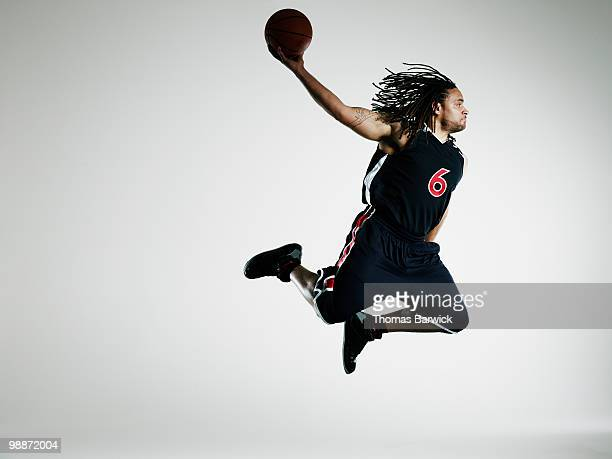 Basketball player in air preparing to dunk ball