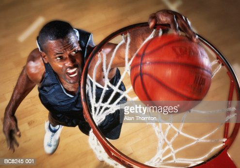 Basketball player jumping below basket, elevated view (Enhancement)
