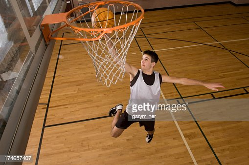 Basketball player jumping in air while trying to score