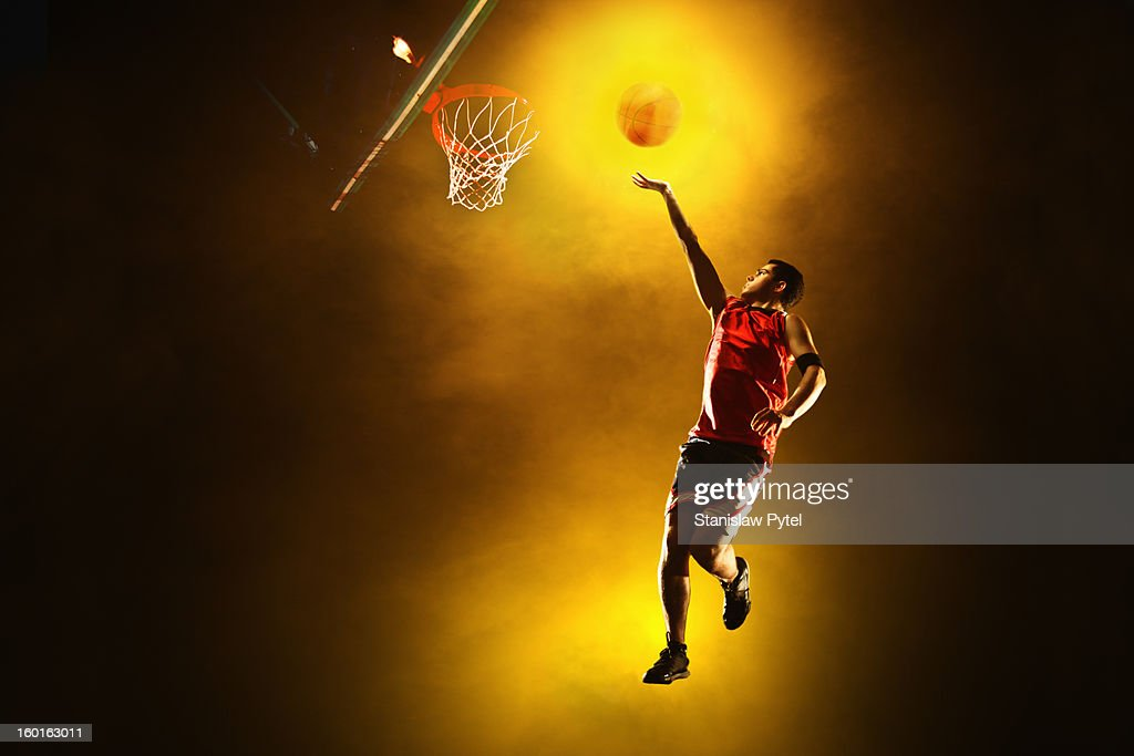 Basketball player jumping with glowing ball : Stock Photo