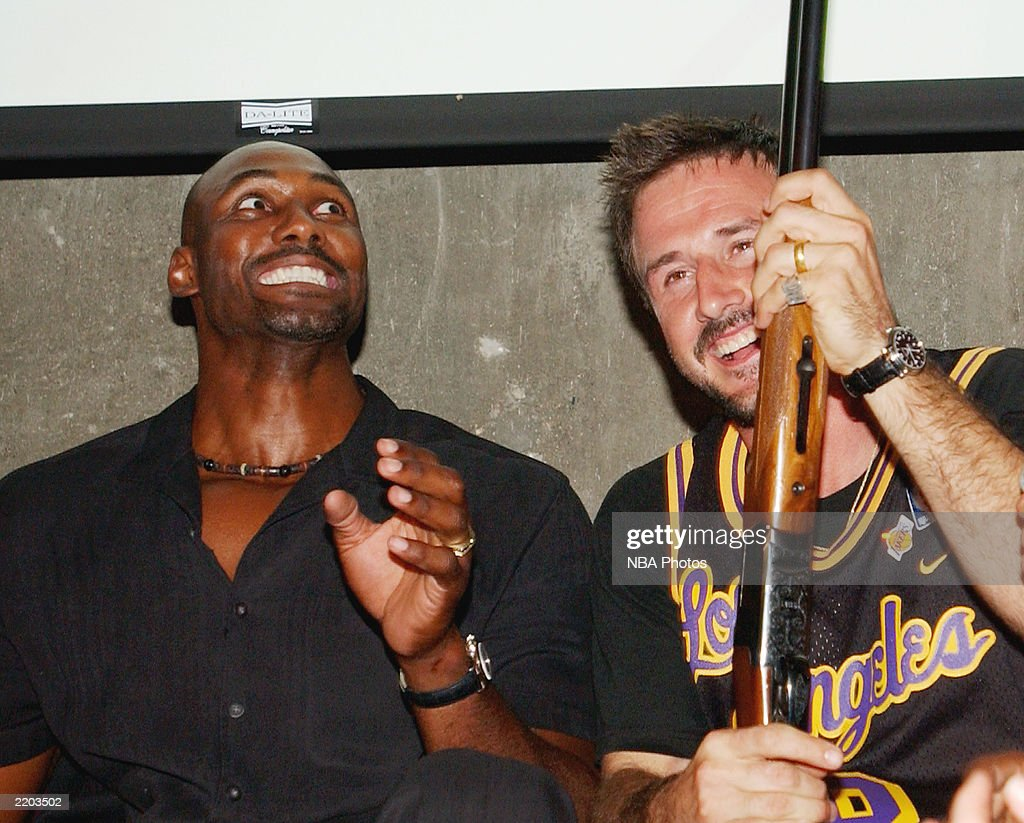Basketball player Karl Malone and actor David Arquette laugh at Karl Malone's gift at a party held for Gary Payton and Karl Malone celebrating both Los Angeles Lakers players' birthdays at the Lucky Strike on July 24, 2003 in Los Angeles, California.