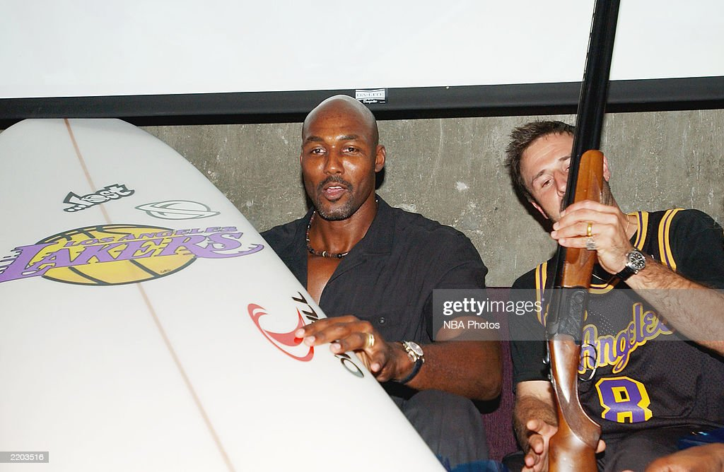 Basketball player Karl Malone and actor David Arquette laugh at Karl Malone's gifts at a party held for Gary Payton and Karl Malone celebrating both Los Angeles Lakers players' birthdays at the Lucky Strike on July 24, 2003 in Los Angeles, California.
