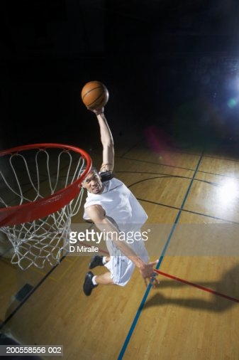 Basketball player leaping to dunk ball