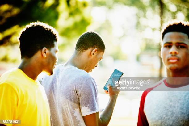 Basketball player looking at smartphone after game