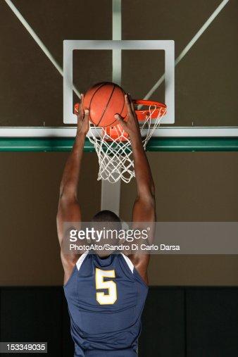 Basketball player making a basket, rear view