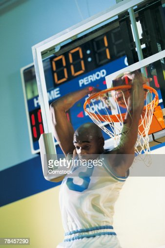 Basketball player making a reverse slam dunk as time expires