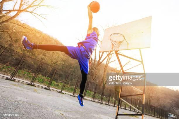 Joueur de basket-ball faisant Dunker sur Cour, à l'extérieur