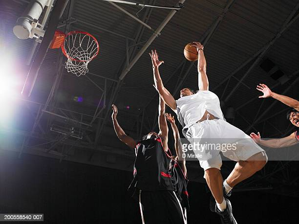 Basketball player playing agianst defenders, low angle view