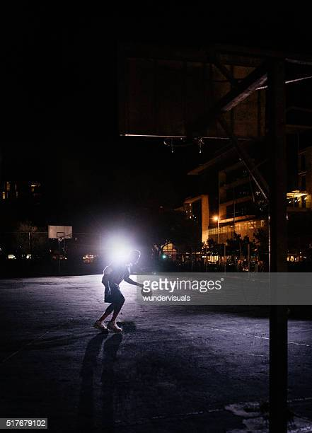 Basketball Player Practicing Alone on Court at Night