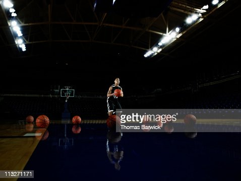 Basketball player practicing free throws in arena : Stock Photo