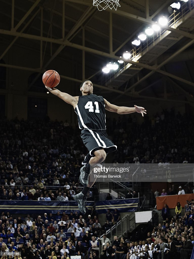Basketball player preparing to dunk ball in arena : Stock Photo