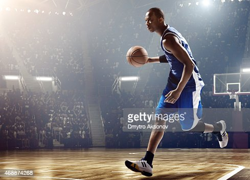 Basketball player running with ball in stadium