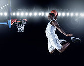 The side view of an african american basketball player scoring an amazing slam dunk in a professional basketball game. This is a composite image and not an actual basketball arena