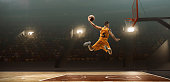 Young muscular basketball player with a ball on floodlight professional court scoring a goal