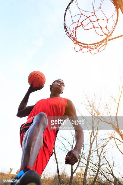 Basketball player scoring slam dunk