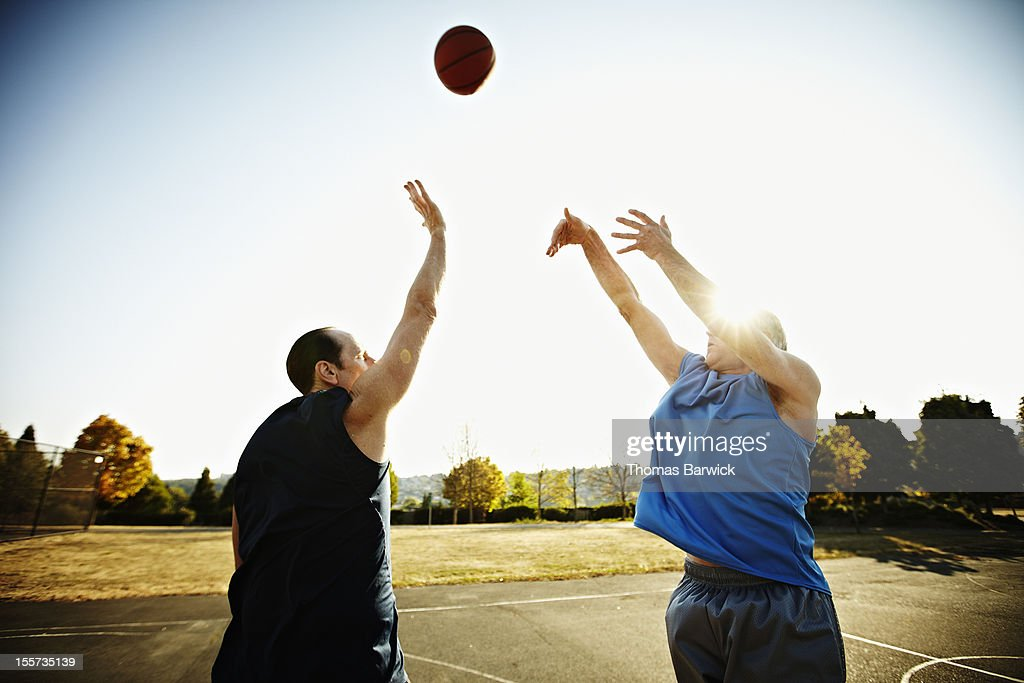 Basketball player shooting over defending player : Stock Photo