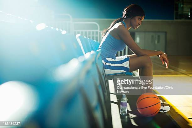 Basketball player sitting in gym