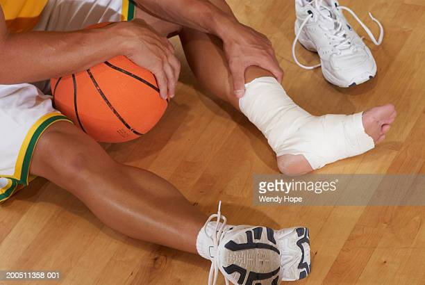 Basketball player sitting with foot in bandage, low section