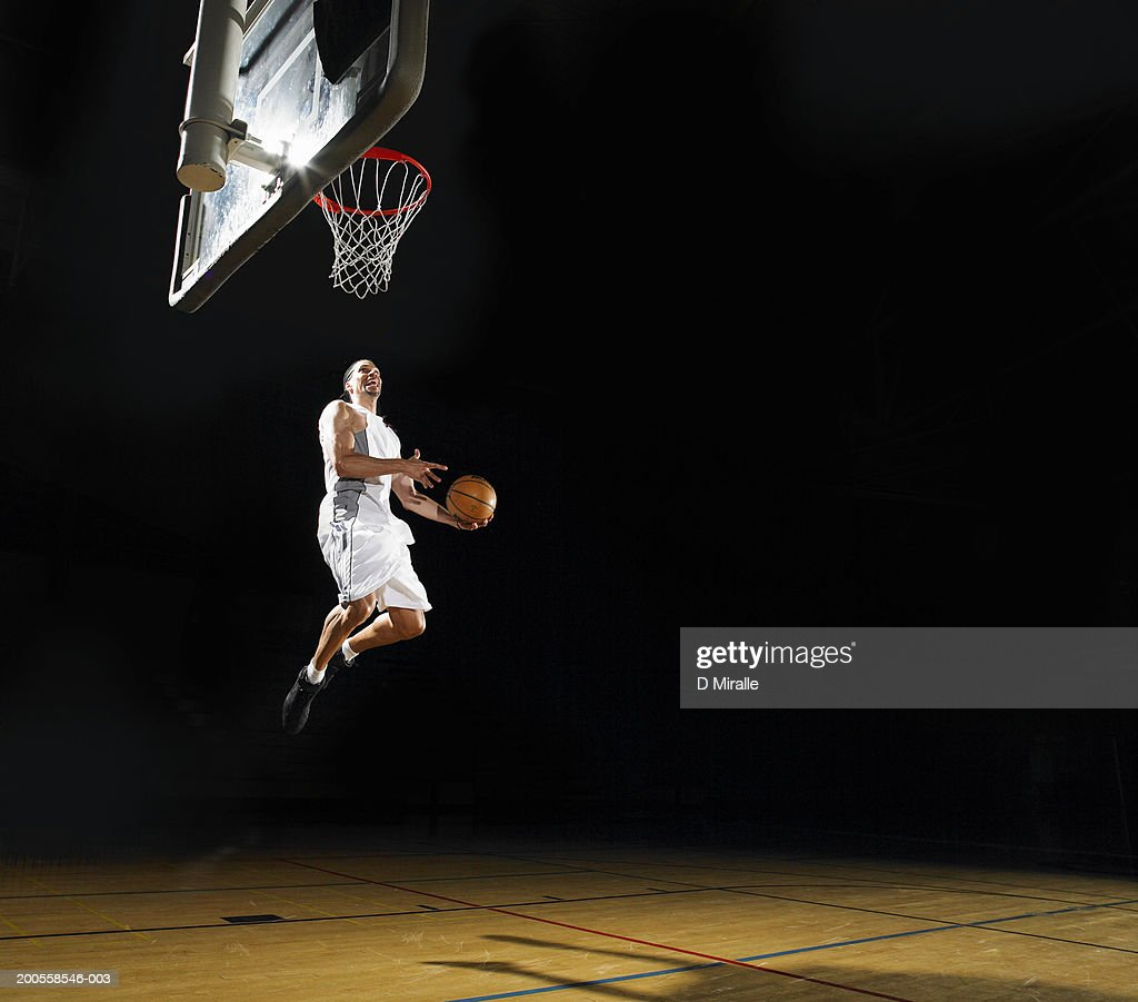 Basketball player slam dunking ball : Stock Photo