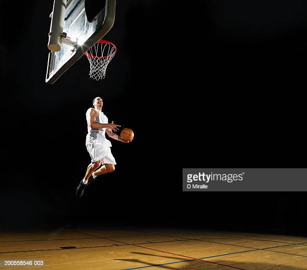 Basketball player slam dunking ball