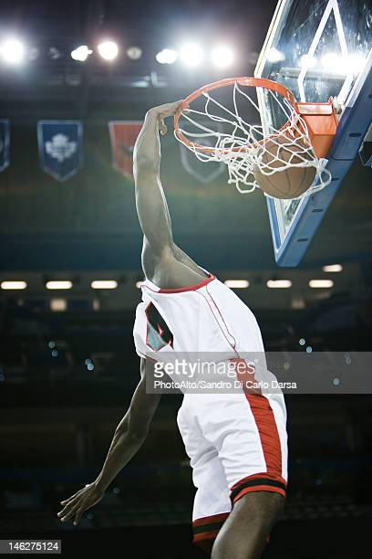 Basketball player slam dunking basketball