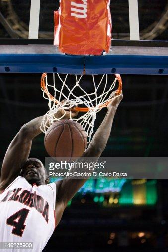 Basketball player slam dunking basketball