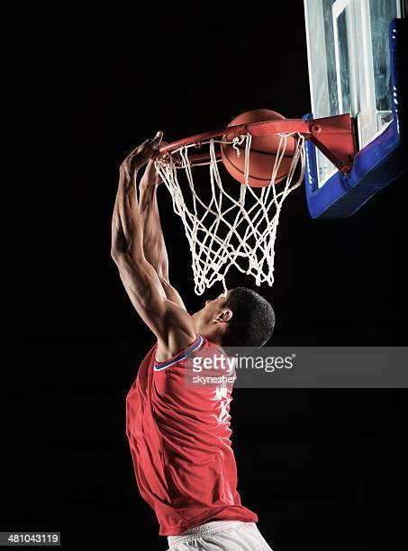 Basketball player slam dunking.