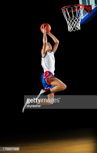 Basketball player slam dunking the ball. : Stock Photo
