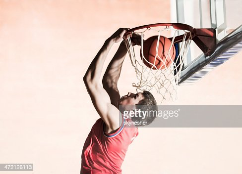 Basketball player slam dunking the ball.