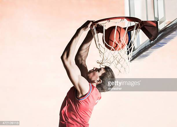 Basketball player slam dunking the ball.