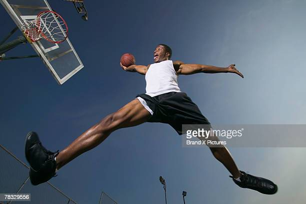 Basketball player slam dunking the ball
