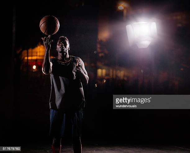 Basketball Player Spinning Ball on Finger on Court in Night