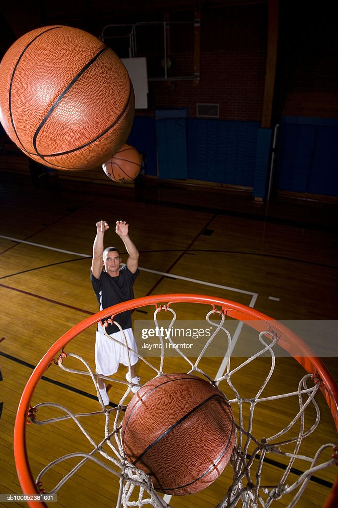 Basketball player throwing ball into basket, elevated view : Stock Photo