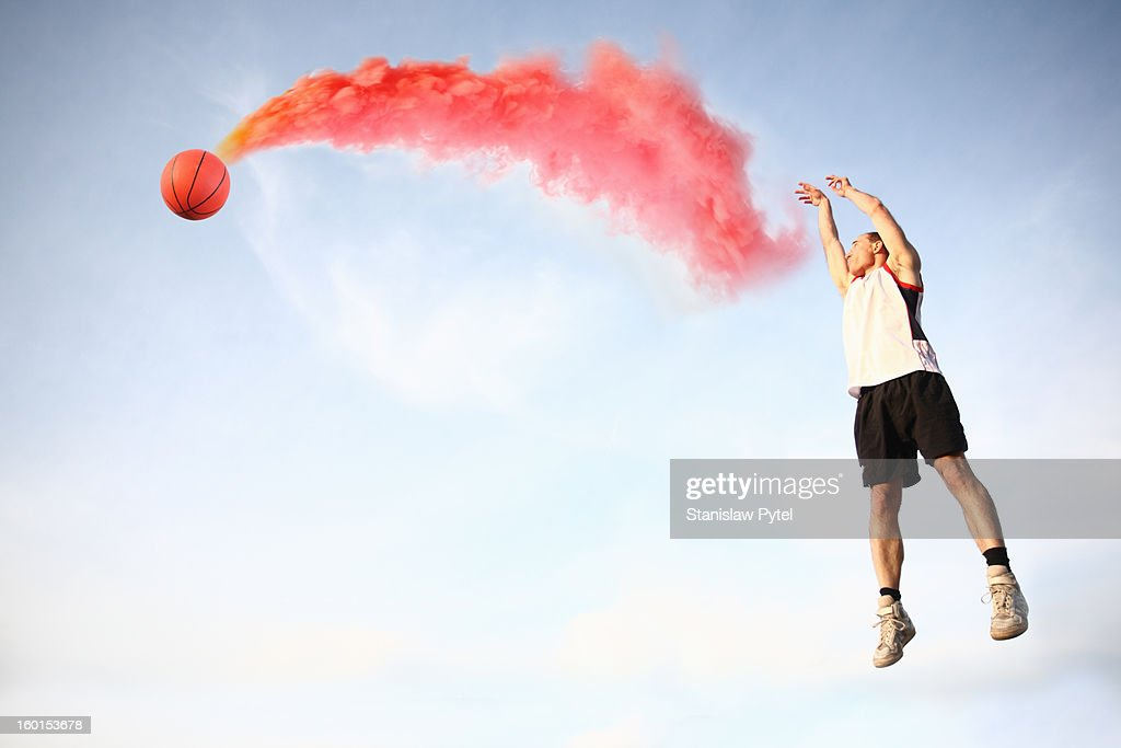 Basketball player throwing smoking ball : Stock Photo